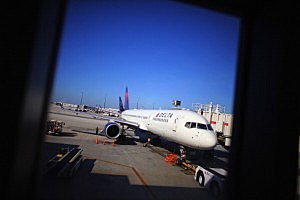 A Delta airlines plane sits at the gate in LaGuardia Airport