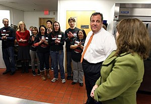 Governor Chris Christie talks with volunteers and Executive Director Marie Reger before serving lunch at Eva's Village in Paterson