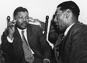 circa 1964: Nelson Mandela, President of the African National Congress (left) in discussion with C Andrews, a Cape Town teacher.