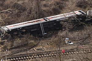 A Metro-North commuter train lies in the brush after it derailed just north of the Spuyten Duyvil station