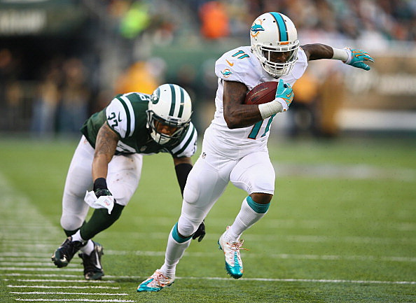 Mike Wallace #11 of the Miami Dolphins scores a touchdown on the missed tackle by  Dee Milliner #27 of the New York Jets i