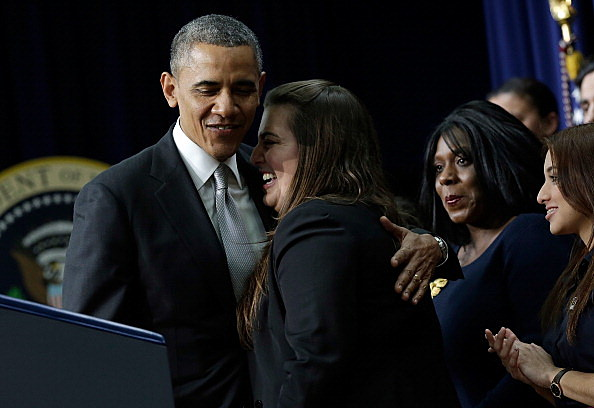 President Barack Obama embraces Monica Weeks, who introduced him and says she also benefitted from provisions of the Affordable Care Act