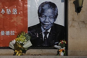 Flowers are placed in front of an image of former South African president Nelson Mandela at the Embassy of South Africa