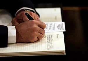 Vice President Joe Biden signs a book of condolences for former South African President Nelson Mandela at the South African Embassy