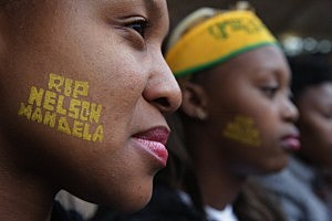 Two young women attend the official memorial service for former South African President Nelson Mandela at FNB Stadium In Johannesburg