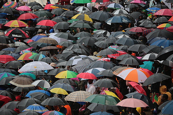 People brave the rain during the Nelson Mandela memorial service at the FNB Stadium In Johannesburg