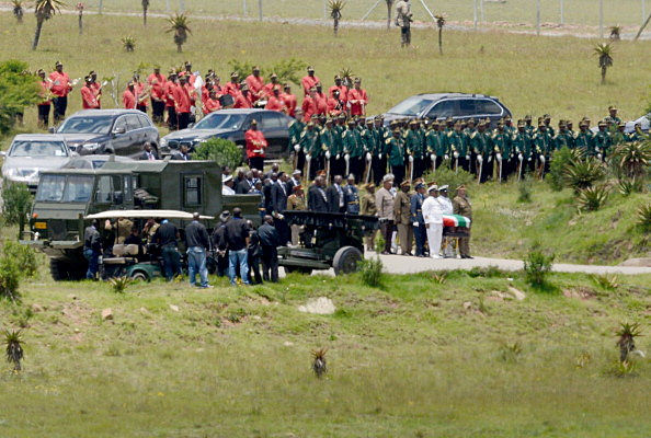The casket of former South African President Nelson Mandela is carried by members of the military for burial on his family's property in his childhood village