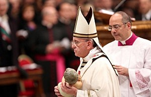 Pope Francis holds the crib as he attends the Christmas night mass at the St. Peter's Basilica