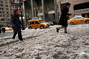 People walk through a cold and snow covered Manhattan