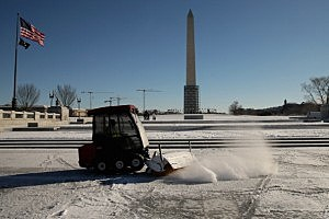 U.S. Park Service equipment works to clear snow and ice from the World War II Memorial on the National Mall