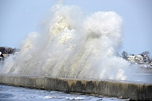 A wave crashes over the sea wall on Winthrop Shore Drive in Massachusetts
