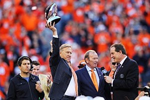 John Elway, executive vice president of football operations for the Denver Broncos, holds  the Lamar Hunt Trophy