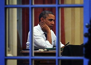 President Barack Obama works on a draft of his State of the Union address in the Oval Office