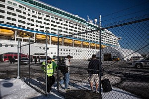 """A guard closes a gate in front of the Royal Caribbean cruise ship """"Explorer of the Sea"""" after it returned to port in Bayonne due to over 600 people became violently sick during a cruise"""
