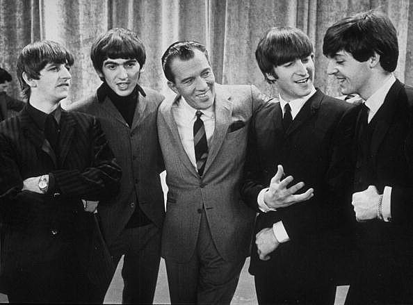 Ed Sullivan smiles while standing with the Beatles on the set of his CBS variety show