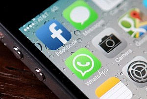 The Facebook and WhatsApp app icons are displayed on an iPhone