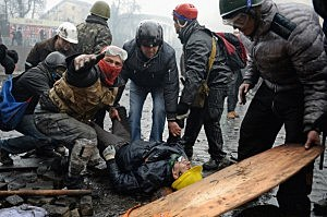 Anti-government protesters carry the injured during continued clashes with police in Independence square,