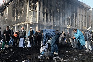 Anti-government protesters clean up debris following continued clashes with police in Independence Square