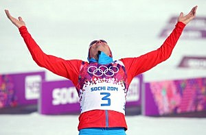 Gold medalist Alexander Legkov of Russia celebrates during the flower ceremony for the Men's 50 km Mass Start Free