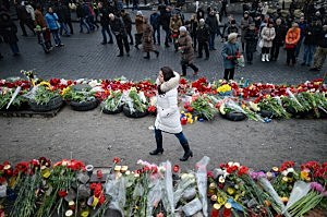A woman walks past flowers left for anti-government demonstrators killed in clashes with police