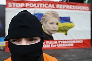 A masked man stands in front of a poster of Yulia Tymoshenko in Independence Square in Kiev, Ukraine