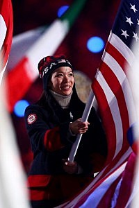 Hockey player Julie Chu of the United States enters with the flag during the 2014 Sochi Winter Olympics Closing Ceremony