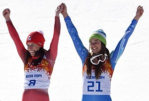 Gold medalists Dominique Gisin of Switzerland (L) and Tina Maze of Slovenia celebrate during the flower ceremony for during the Alpine Skiing Women's Downhill