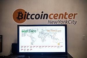 A television screen displays various bitcoin rates at Bitcoin Center NYC