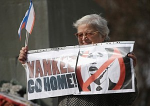 "Pro-Russian sympathizers, including an elderly woman holding a sign that reads: ""Yankee Go Home!"", attend an anti-American rally hours after heavily-armed, unidentifed soldiers took up positions around the nearby Crimean Parliament"