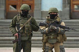 Heavily-armed troops displaying no identifying insignia and who were mingling with local pro-Russian militants stand guard outside a local government building in Simferopol, Ukraine.
