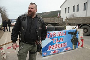 """A pro-Russian militant who identifed himself as Nazar and says he is a member of the """"Night Wolves"""" biker club helps man a checkpoint next to a sign that reads: """"Where we are, there is Russia"""" on a road leading to Sevastopol in Crimea"""