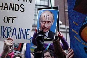 People hold signs during a protest in front on the Russian Consulate against Russian military intervention in the Crimea region of Ukraine  in New York City.