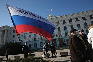 A Russian flag stands outside a local government building where pro-Russian militants and heavily-armed troops displaying no identifying insignia stood guard on  in Simferopol, Ukraine.