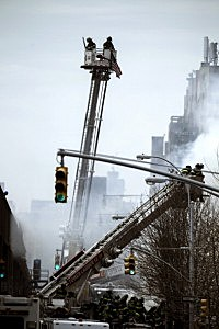 Firefighters respond to a five-alarm fire and building collapse
