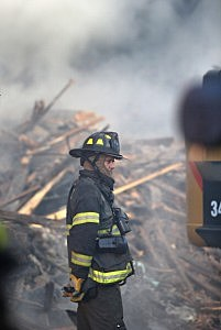 A fireman watches as work crews remove debris from the site of an explosion in East Harlem