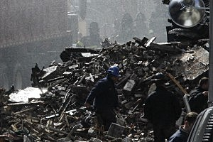 Firefighters remove debris from the smoking site of an explosion in East Harlem