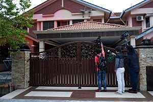 Members of the international press attempt to to get someone to speak to them in front of the house of Fariq Abdul Hamid, the missing Malaysian airliner's co-pilot in Shah Alam