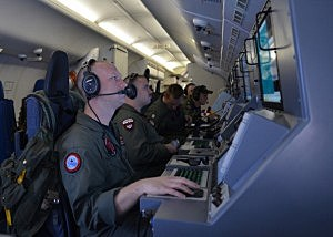 In this handout provided by the U.S. Navy, Crew members on board a P-8A Poseidon assigned to Patrol Squadron (VP) 16 man their workstations while assisting in search and rescue operations for Malaysia Airlines flight MH370