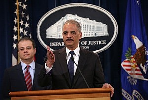 U.S. Attorney General Eric Holder (R) speaks as U.S. Attorney for the Southern District of New York Preet Bharara (L) listens during an announcement at the Justice Department