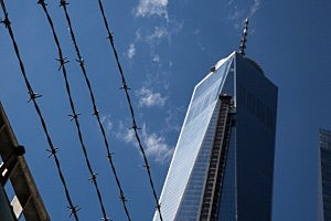 A barbed wire fence guards Ground Zero and One World Trade Center