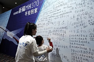 A Chinese girl and her mother of a passenger from the missing Malaysia Airlines flight MH370 writing on a clifford slogans board at the Lido Hotel in Beijing China.
