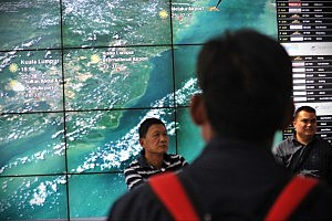 A passenger views a weather map in the departures terminal of Kuala Lumpur International Airport