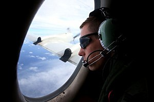 RAAF Airbourne Electronics Analyst Bodine Luscott keeps watch for debris onboard an AP-3C Orion whilst on a search mission in the Southern Indian Ocean