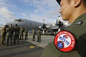 South Korean Navy Lieutenant Commander Oh Kang-Min (R) is pictured wearing a MH370 search and rescue team patch on his sleeve as he waits to meet Australian Prime Minister Tony Abbott in front of a Royal Australian Air Force AP-3C Orion aircraft at RAAF Base Pearce in Perth, Australia.