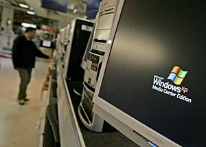 A customer looks at a display of computers running the Microsoft Windows XP software