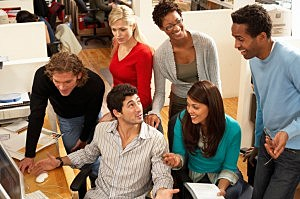 Group of office workers gathered around one workstation