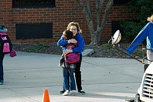 Monroe Principal Lynda Zapoticzny hugs a student arriving at Middlesex Community College for class
