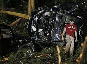 A searcher walks past the remains of a SUV in Louisville, Miss
