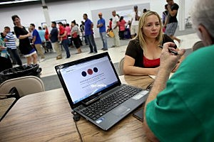 Norma Licciardello sits with an agent from Sunshine Life and Health Advisors as they wait for the Affordable Care Act website to come back on line in Florida