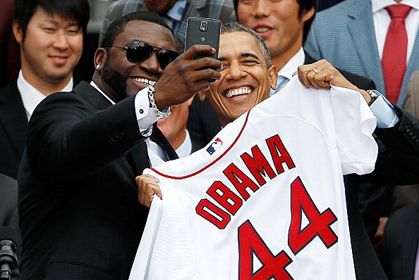 """Boston Red Sox designated hitter David Ortiz (L) poses for a """"selfie"""" with President Barack Obama during a ceremony on the South Lawn of the White House to honor the 2013 World Series Champion Boston Red Sox"""